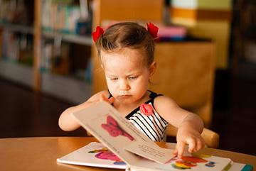 ребенок изучает книги